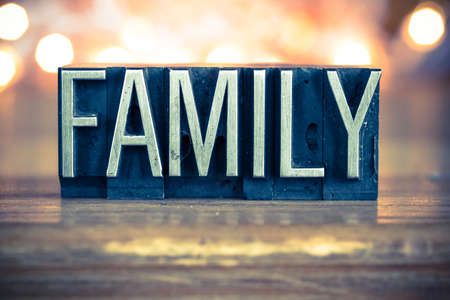 The word FAMILY written in vintage metal letterpress type on a soft backlit background. 版權商用圖片