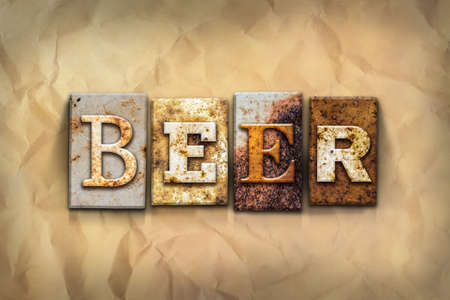 crumbled: The word BEER written in rusty metal letterpress type on a crumbled aged paper background. Stock Photo
