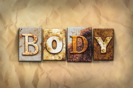 crumbled: The word BODY written in rusty metal letterpress type on a crumbled aged paper background.