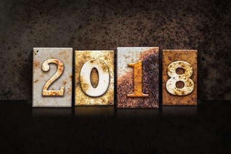 rusty background: The word 2018 written in rusty metal letterpress type on a dark textured grunge background. Stock Photo