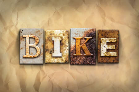 crumbled: The word BIKE written in rusty metal letterpress type on a crumbled aged paper background.