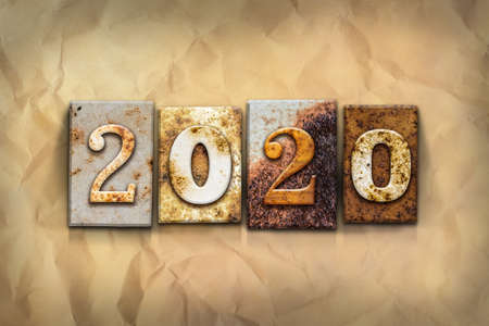 crumbled: The word 2020 written in rusty metal letterpress type on a crumbled aged paper background.
