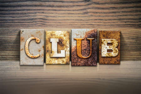 clique: The word CLUB written in rusty metal letterpress type sitting on a wooden ledge background. Stock Photo