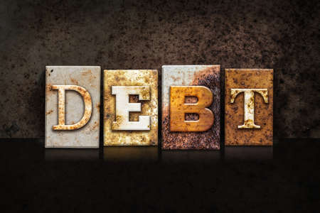 The word DEBT written in rusty metal letterpress type on a dark textured grunge background. Stock Photo