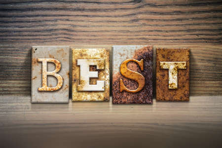 accolade: The word BEST written in rusty metal letterpress type sitting on a wooden ledge background. Stock Photo