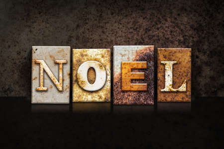 hymn: The word NOEL written in rusty metal letterpress type on a dark textured grunge background. Stock Photo