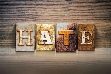The word HATE written in rusty metal letterpress type sitting on a wooden ledge background.