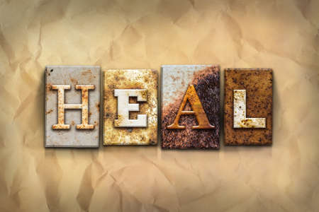 The word HEAL written in rusty metal letterpress type on a crumbled aged paper background.