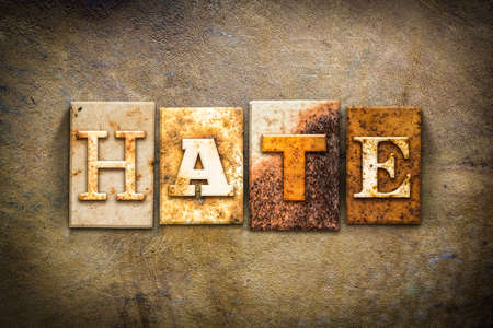 abomination: The word HATE written in rusty metal letterpress type on an old aged leather background.