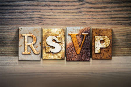 rsvp: The word RSVP written in rusty metal letterpress type sitting on a wooden ledge background. Stock Photo
