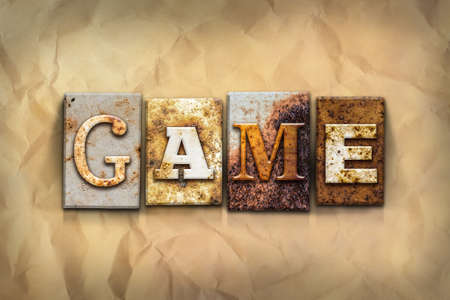 athletic type: The word GAME written in rusty metal letterpress type on a crumbled aged paper background. Stock Photo