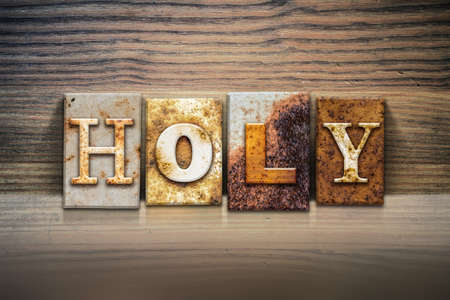sanctified: The word HOLY written in rusty metal letterpress type sitting on a wooden ledge background. Stock Photo