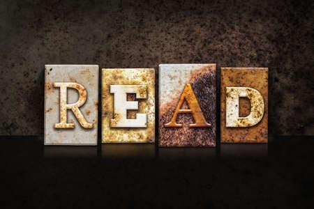 recite: The word READ written in rusty metal letterpress type on a dark textured grunge background. Stock Photo