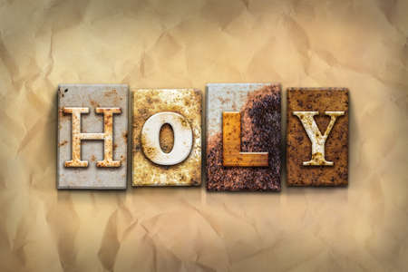 godly: The word HOLY written in rusty metal letterpress type on a crumbled aged paper background. Stock Photo
