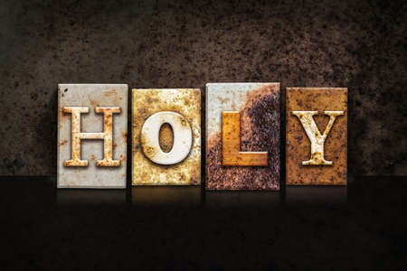 The word HOLY written in rusty metal letterpress type on a dark textured grunge background.