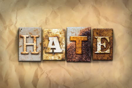 The word HATE written in rusty metal letterpress type on a crumbled aged paper background. Stock Photo