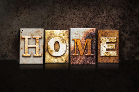 homecoming: The word HOME written in rusty metal letterpress type on a dark textured grunge background. Stock Photo