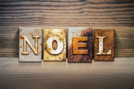 hymn: The word NOEL written in rusty metal letterpress type sitting on a wooden ledge background. Stock Photo