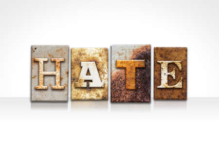 The word HATE written in rusty metal letterpress type isolated on a white background.
