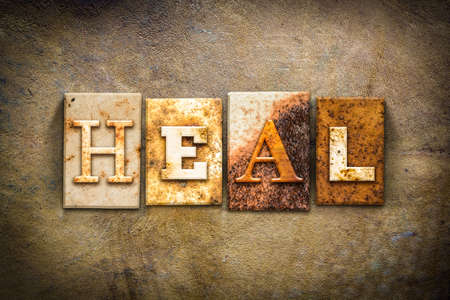 The word HEAL written in rusty metal letterpress type on an old aged leather background.