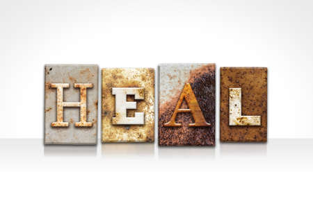The word HEAL written in rusty metal letterpress type isolated on a white background. Stock fotó