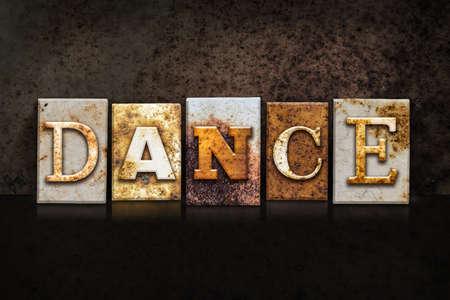 The word DANCE written in rusty metal letterpress type on a dark textured grunge background. Stock Photo