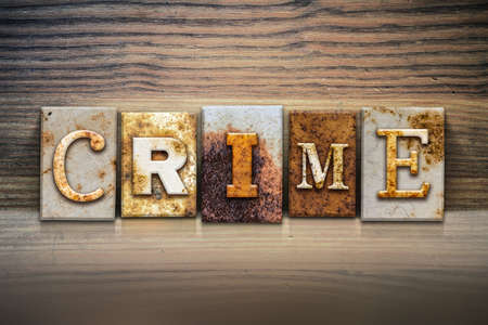 crook: The word CRIME written in rusty metal letterpress type sitting on a wooden ledge background.