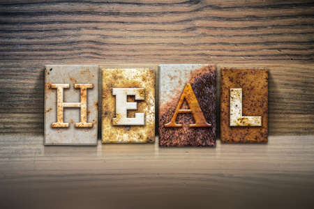 The word HEAL written in rusty metal letterpress type sitting on a wooden ledge background.