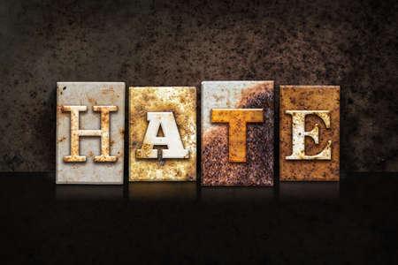 The word HATE written in rusty metal letterpress type on a dark textured grunge background.