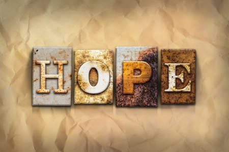 hope: The word HOPE written in rusty metal letterpress type on a crumbled aged paper background. Stock Photo