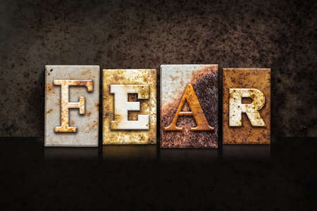 fear: The word FEAR written in rusty metal letterpress type on a dark textured grunge background.