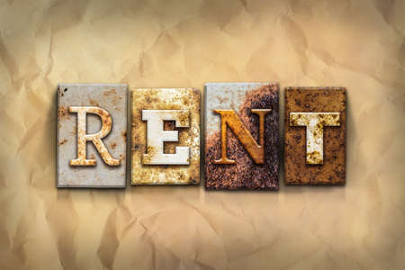 apartment for rent: The word RENT written in rusty metal letterpress type on a crumbled aged paper background. Stock Photo