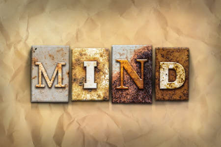 crumbled: The word MIND written in rusty metal letterpress type on a crumbled aged paper background. Stock Photo