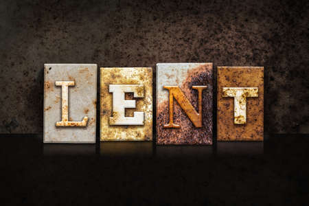 atonement: The word LENT written in rusty metal letterpress type on a dark textured grunge background. Stock Photo