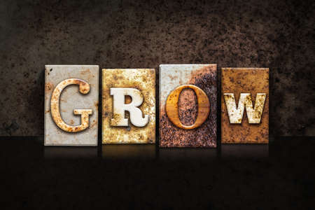 text word: The word GROW written in rusty metal letterpress type on a dark textured grunge background.