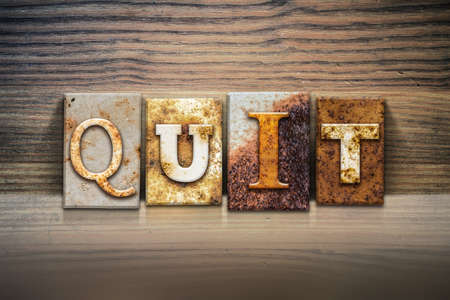 The word QUIT written in rusty metal letterpress type sitting on a wooden ledge background.