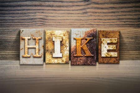 appalachian trail sign: The word HIKE written in rusty metal letterpress type sitting on a wooden ledge background.
