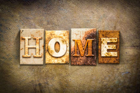 homecoming: The word HOME written in rusty metal letterpress type on an old aged leather background. Stock Photo