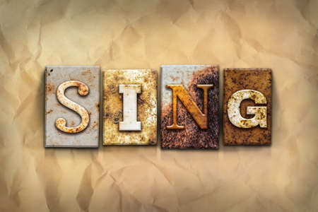 chorale: The word SING written in rusty metal letterpress type on a crumbled aged paper background.