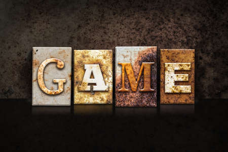 word game: The word GAME written in rusty metal letterpress type on a dark textured grunge background. Stock Photo