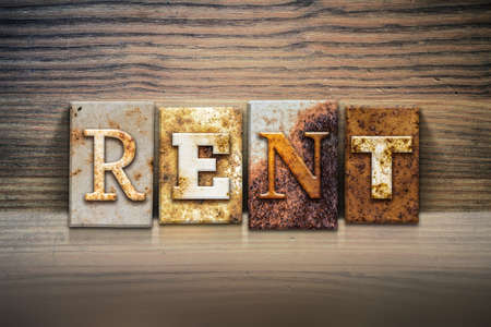 renter: The word RENT written in rusty metal letterpress type sitting on a wooden ledge background.