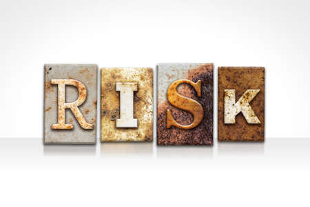 dangerous ideas: The word RISK written in rusty metal letterpress type isolated on a white background.