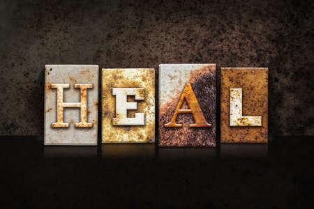 The word HEAL written in rusty metal letterpress type on a dark textured grunge background.