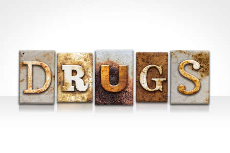 The word DRUGS written in rusty metal letterpress type isolated on a white background.