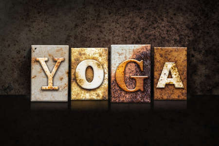 word: The word YOGA written in rusty metal letterpress type on a dark textured grunge background. Stock Photo