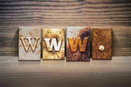 The word www. written in rusty metal letterpress type sitting on a wooden ledge background.