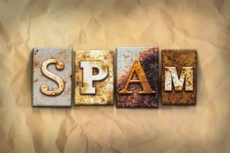 soliciting: The word SPAM written in rusty metal letterpress type on a crumbled aged paper background. Stock Photo