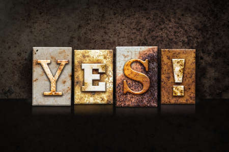affirmative: The word YES! written in rusty metal letterpress type on a dark textured grunge background.