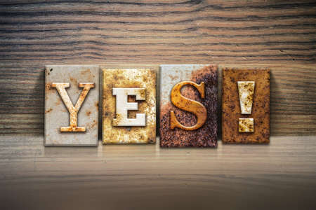 validation: The word YES! written in rusty metal letterpress type sitting on a wooden ledge background. Stock Photo