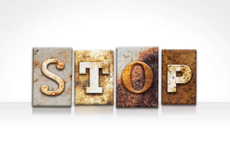 standstill: The word STOP written in rusty metal letterpress type isolated on a white background. Stock Photo